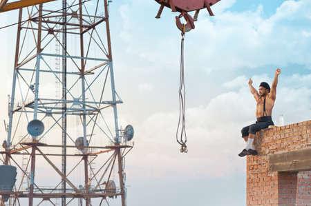 Good day. Retro builder man enjoying a sunny day resting on the skyscraper under construction 版權商用圖片