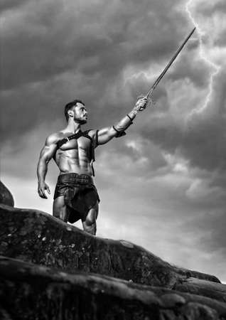 No one he fears. Monochrome low angle shot of a fearless muscular warrior with a sword in his hand posing under stormy sky on a mountain peak Archivio Fotografico