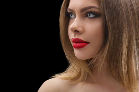 Tempting beauty. Closeup studio portrait of a beautiful young girl wearing classic makeup with red lips posing on black background