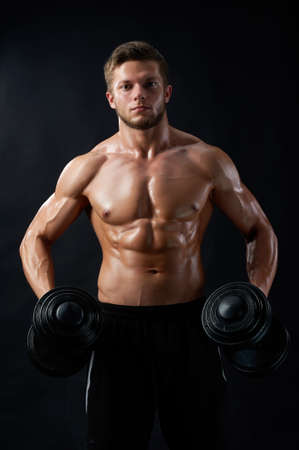 Portraying masculinity. Cropped shot of a ripped fitness man working out with dumbbells showing off his muscles