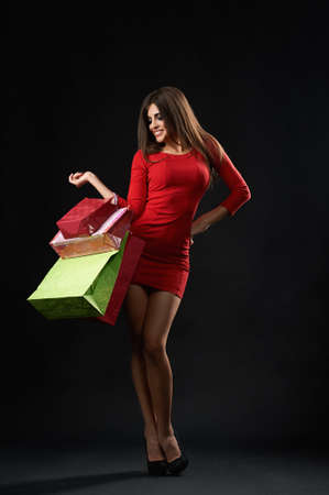 Studio shot of a gorgeous young brunette woman posing with her shopping bags on black background shopaholic buying purchasing happiness emotions expressive. 版權商用圖片