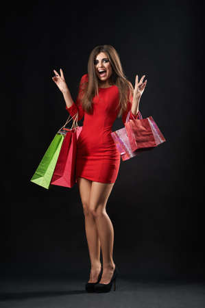 Vertical studio shot of a beautiful woman looking excited holding her shopping bags happiness emotions buyer shopper consumer wellbeing lifestyle shop store consumerism customer concept.