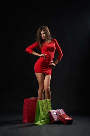 Shot of a young sexy woman wearing red dress posing seductively with shopping bags buyer shopper consumerism consumer customer shopaholic concept.