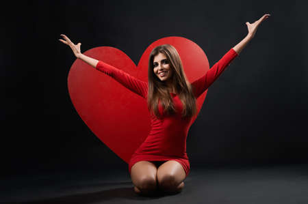 Horizontal studio shot of a happy young beautiful woman in a red dress posing excitedly in front of a big red heart love peace happiness relationships concept.