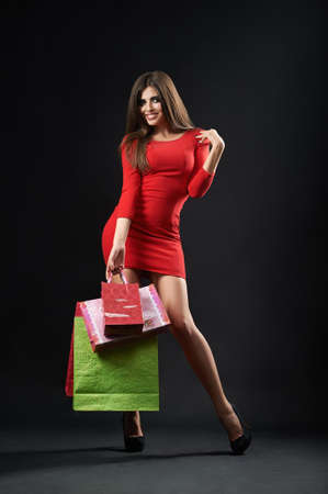 Full length studio shot of a gorgeous young woman in a red dress smiling joyfully holding bunch of shopping bags on black background consumerism buying shopaholic purchasing concept. 版權商用圖片