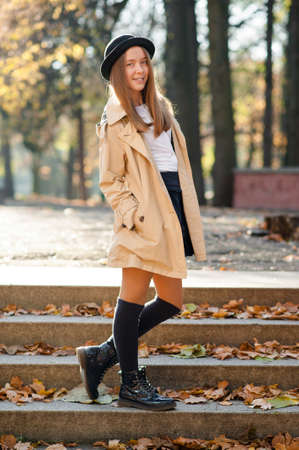 Young yet stylish. Soft focus portrait of a cute teen girl posing in autumn park outdoors 版權商用圖片