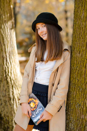 Love wandering alone. Soft focus shot of a happy smiling teen holding a book posing near a tree 版權商用圖片