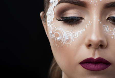 Closer look. Cropped closeup of a professional bridal lace makeup on a young beautiful woman on black background