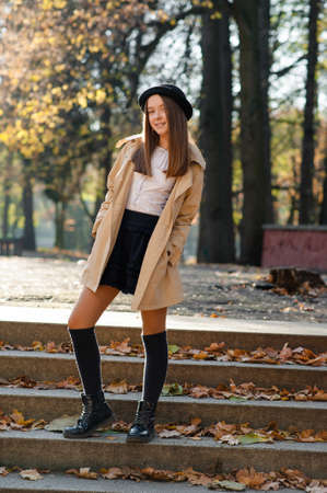 Casually dressed. Beautiful teen girl posing on the steps in an autumn park smiling to the camera soft focus 版權商用圖片