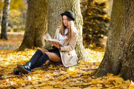 Her quiet place. Horizontal portrait of a beautiful young girl reading a book sitting near a tree soft focus