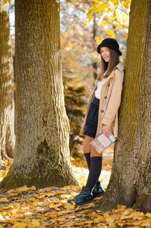 Having a walk. Full length portrait of a cute teenager girl standing near the tree smiling joyfully soft focus 版權商用圖片