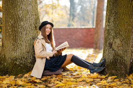 So peaceful here. Soft focus portrait of a pretty girl holding a book smiling resting in the forest