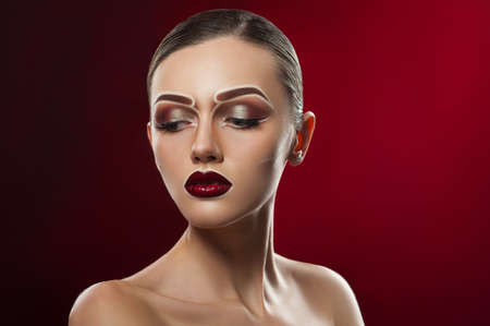 Red lady. Studio portrait of a young female model wearing professional makeup against red background copyspace on the side