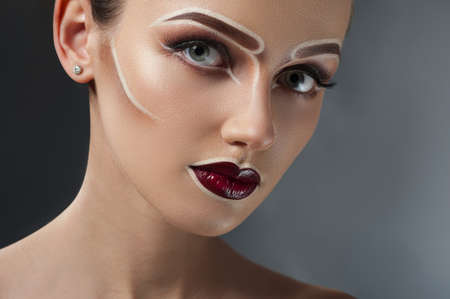 Scenic look. Studio closeup shot of a beautiful female model posing with professional scenic art makeup looking to the camera