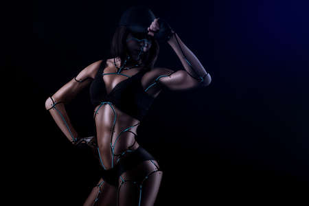 Futuristic beauty. Beautiful fitness woman photoshopped into a robot posing in blue artistic lighting on black background 版權商用圖片