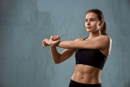 Front view of fit caucasian female model stretching arm, wearing black sportswear standing and looking aside, isolated on loft gray studio background. Muscular pretty young fitnesswoman.