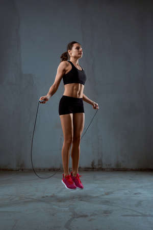 Side view of pretty female bodybuilder in black sport suit with perfect body using skipping rope in gym. Young athletic brunette woman jumping in hall, loft gray atmosphere. Concept of sport. 版權商用圖片