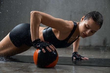 Side view of wet female bodybuilder in sports underwear doing push up using small ball under hand on floor, loft interior. Muscular woman training upper body muscles on mat under rain. Sport concept. 版權商用圖片