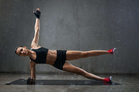 Muscular wet young woman training on floor on mat in empty hall under rain, loft interior. Female bodybuilder in gloves practicing side plank exercise with hand and leg up indoors. Concept of sport. 版權商用圖片