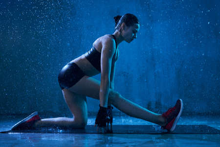Side view of fit female model stretching leg before training on mat, isolated in darkness with blue light under rain. Muscular wet flexible young fitnesswoman posing in black sports underwear indoor.