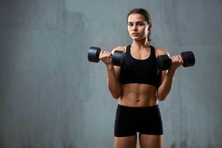Isolated portrait of pumped fitnesswoman in black sportswear posing on gray studio background, loft interior. Front view of muscular caucasian woman training with dumbbells and looking at camera. 版權商用圖片