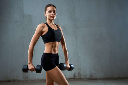 Side view of muscular pretty woman carrying dumbbells and looking at camera. Isolated portrait of pumped smiling fitnesswoman in black sports underwear posing on gray loft studio background.