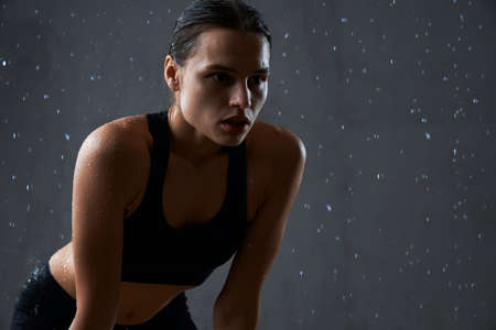 Close up of muscular fitnesswoman posing under rain. Crop of wet fit female model holding hands on knees, wearing black sportswear having rest after hard training, isolated on gray. 版權商用圖片