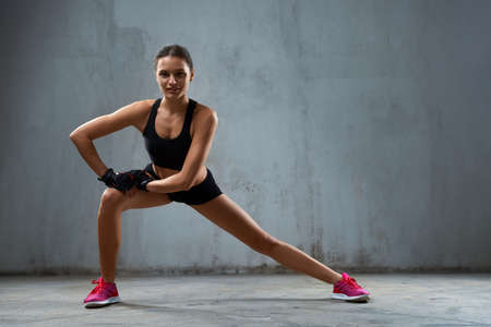 Front view of young female training legs and smiling. Muscular sportswoman with perfect body doing side lunges and looking at camera in empty hall, gray loft interior. Concept of healthy lifestyle.