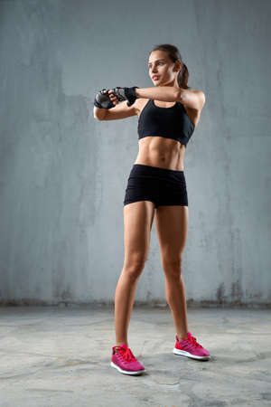 Full length portrait of fit female model stretching arms before training, isolated on loft gray studio background. Muscular flexible young fitnesswoman posing in black sports underwear indoor.