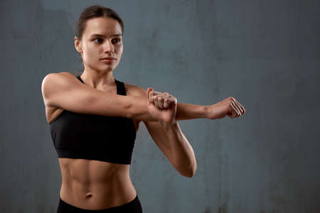 Close up portrait of fit female model stretching arm before training, isolated on loft gray studio background. Muscular flexible young fitnesswoman posing in black sports underwear indoor.