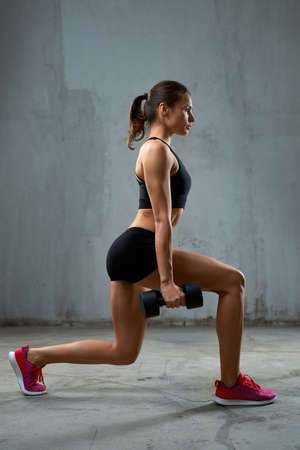 Side full length portrait of female bodybuilder training legs using dumbbells. Muscular sportswoman with perfect body doing lunges indoors, loft interior. Concept of bodybuilding, healthy lifestyle.