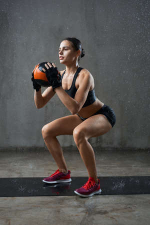 Side view of pretty female bodybuilder in gloves training legs, holding small ball in hands under rain. Wet muscular sportswoman with perfect body doing squats on mat in empty hall, loft interior.