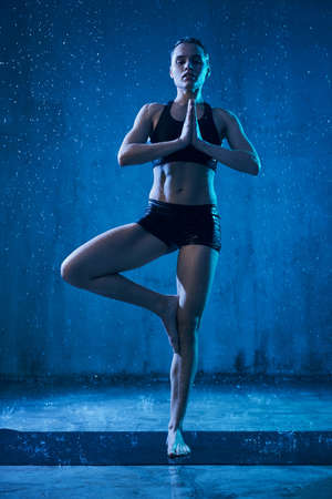 Front view of sporty young woman practicing vrikshasana pose, isolated in loft hall in darkness with blue light. Calm wet woman stanidng on mat under rain and looking at camera. Concept of yoga. 版權商用圖片