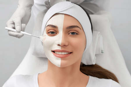 Portrait of smiling young woman lying in beauty salon and beautician applying special white mask on face. Concept of procedure for rejuvenation skin or improvements.