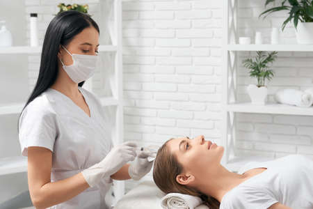 Side view of young woman on procedure for restoration condition and growth hair in professional beauty salon. Concept of improvements hair with special cosmetics.
