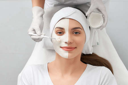 Front view portrait of beautician in white rubber gloves doing special beauty procedure for young smiling woman. Concept of improvements skin with cosmetics in beauty salon.