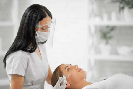 Side view of beautiful beautician in protective mask doing injection tighten skin from wrinkles in professional beautician. Concept of process injection for improve the condition face.
