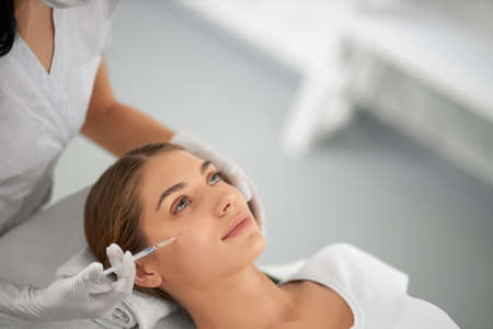 Side view portrait of smiling beautiful young woman in white shirt doing procedure for improvements face skin. Concept of special cosmetics injection for anti-aging in beauty salon.