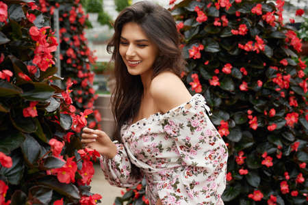 Pretty cheerful woman with professional makeup and hairstyle standing at greenhouse full of blooming flowers. Beauty of people and nature.