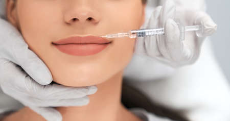 Close up of beautician in white rubber gloves doing injection in lips for young beautiful woman. Concept of process augmentation and improvement lips in professional salon.