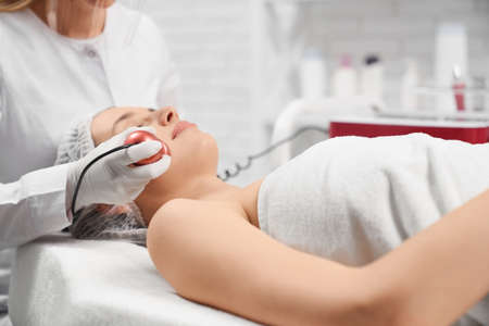 Side view of young beautiful woman lying on procedure for face in beautician. Concept of special beauty procedure anti-aging and improvements skin with cosmetics.