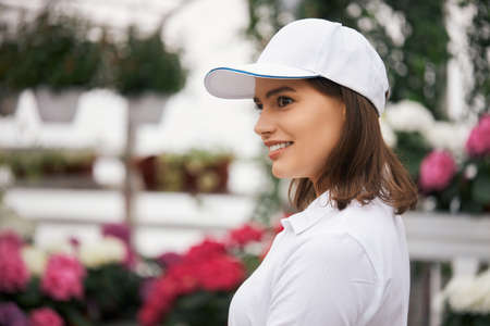 Pleasant woman in white cap and t-shirt posing at greenhouse with various colorful flowers growing in pots. Concept of plants and farming.