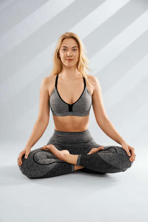 Close up of sporty blonde young woman doing yoga practice isolated on grey background. Concept of healthy life and natural balance between body and mental development.