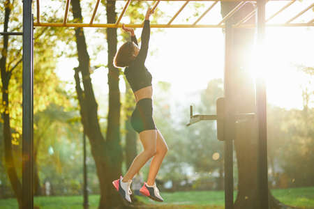 Young sports woman hanging on horizontal bar during workout on fresh air. Active brunette in sport outfit training abdominal muscles at outdoor sport ground.