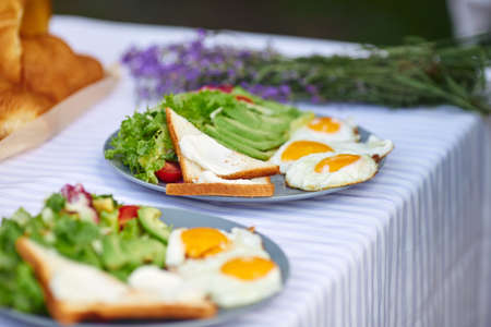 Selective focus of fresh appetizers for two and aromatic lavender bouquet. Close up view of beautiful table decoration outdoors, fresh salad with eggs and toasts. Concept of cuisine, food. 版權商用圖片