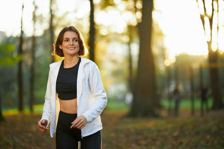 Beautiful young lady with short brown hair feeling happy during outdoors sport activity. Smiling woman doing physical exercises at city park.