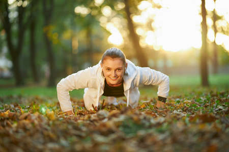 Fit and healthy young female dressed in sport clothing practicing plank position on fresh air. Happy woman with brown hair smiling and looking at camera. 版權商用圖片