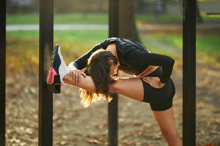 Fitness young woman in sport clothing flexing body on horizontal bar outdoors. Active brunette having morning training at city park.