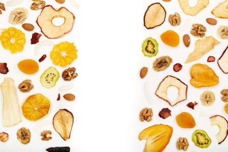 Above view of well laid out dried fruits apples, mango, orange, dried apricots, kiwi, dried coconut and walnuts on white background. Concept of organic healthy assorted dried fruit for snacks.