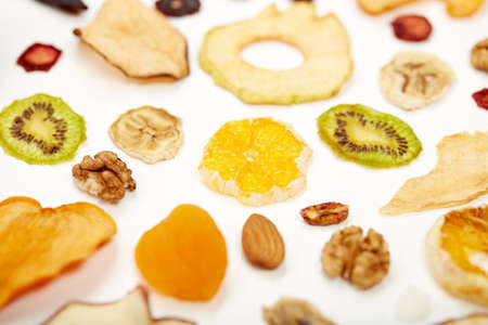 Close up of healthy food dried apples, orange, dried apricots, kiwi, dried coconut and walnuts on white background. Concept of proper nutrition with tasty of dried fruits and nuts. 版權商用圖片